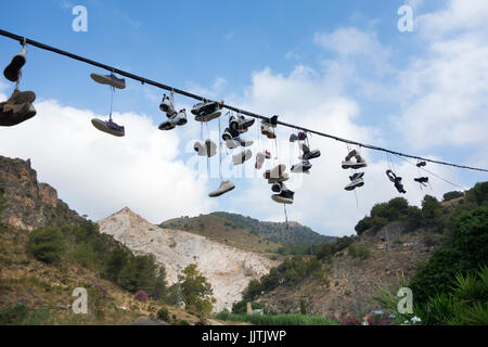 Lots of trainers or running shoes hanging from a cable in Spain - Stock Photo
