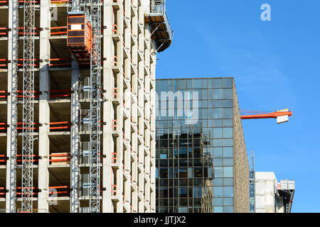 Front view of a glass building between two concrete buildings under construction with a red tower crane against - Stock Photo