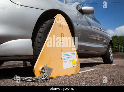 An untaxed car clamped by the DVLA - Stock Photo