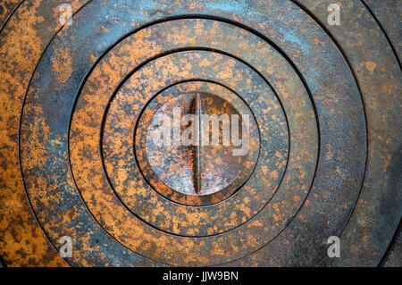 Abstract metal background with geometric holes in a circle and texture rust orange-brown with spots. - Stock Photo