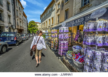 Solo lady traveler sightseeing as she passes by a lavender shop in the French town of Avignon in the Provence region - Stock Photo