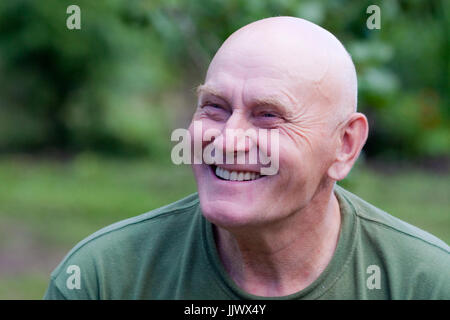 Photo of a smiling grandfather looking at the distance - Stock Photo