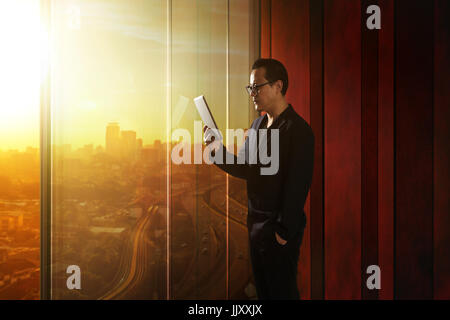 Young asian businessman holding and using digital tablet . Sunrise scene . - Stock Photo