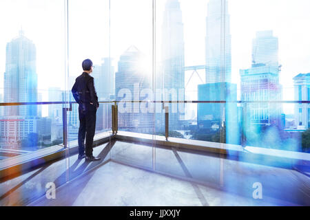 Young businessman looking out the city in the office . morning scene. . - Stock Photo