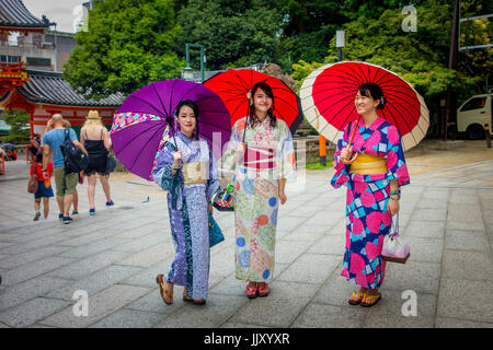 KYOTO, JAPAN - JULY 05, 2017: Young Japanese women wearing traditional Kimono and holding umbrellas in their hands - Stock Photo