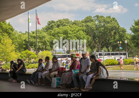 Washington, DC - Visitors to the National Museum of African American History and Culture sit by a pool outside the museum.