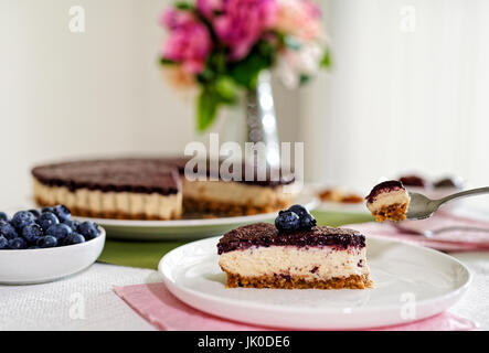 Vegan Cheesecake with blueberries, cashew nuts and dates - Stock Photo