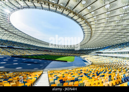 rows of yellow and blue stadium seats on soccer field stadium - Stock Photo