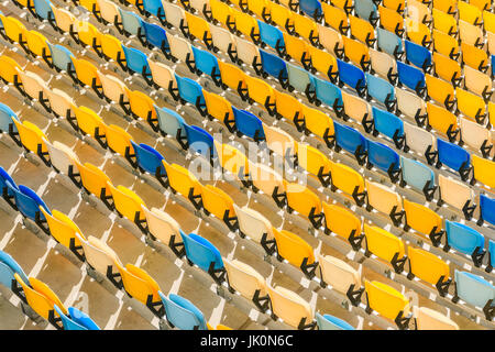 elevated view of rows of yellow and blue stadium seats background - Stock Photo