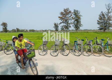 Two boys on one bike speed round the corner by a rice paddy - Hoi An - 13 March 2017 - Stock Photo