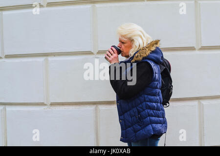 Side portrait of a blonde woman with a coffee to go. - Stock Photo
