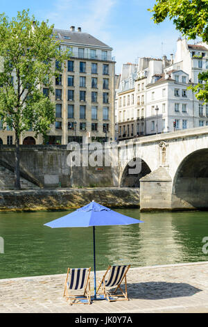 Two blue and white striped deck chairs in the sun under a blue parasol on the bank of the river Seine with typical - Stock Photo