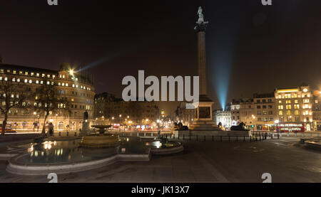 Trafalgar Square fountains at night with buses and Whitehall behind, West End, London, UK - Stock Photo