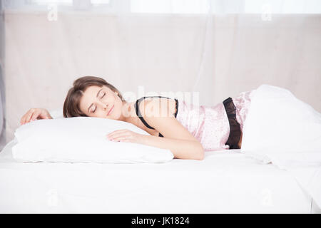 girl in pajamas asleep in the morning on bed - Stock Photo
