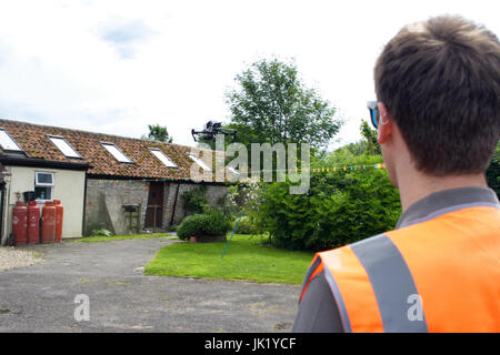 Licensed Drone Operator flying DJI Inspire 1 at a property in the UK - Stock Photo