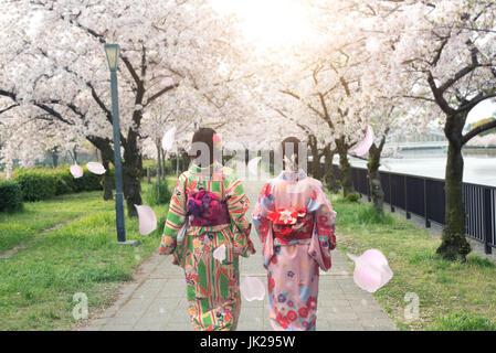 Couple asian women wearing traditional japanese kimono in sakura garden in Osaka, Japan. - Stock Photo
