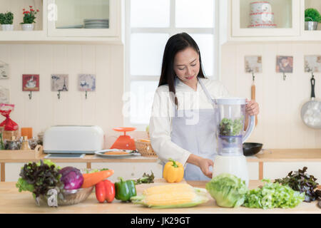 Vegetable smoothie. Asian woman making green smoothies with blender home in kitchen. Healthy raw eating lifestyle - Stock Photo