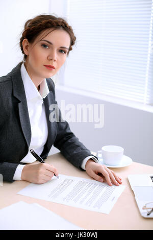 Business woman looks like yulia tymoshenko is sitting at the table and working in  white colored office . Ukrainian - Stock Photo