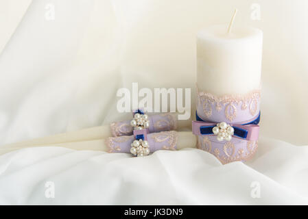 Wedding decorated candles with the bowknots and pearls in tenderly blue and violet colors - Stock Photo