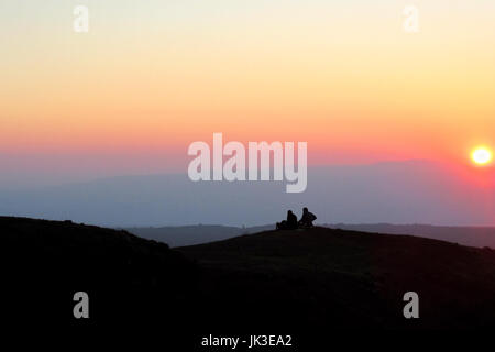 A couple sit on a hill silhouetted by the setting sun near Mount Bental in Israel's Golan Heights. - Stock Photo
