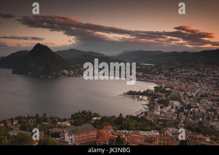 Switzerland, Ticino, Lake Lugano, Lugano, town view and Monte San Salvador from Monte Bre, sunset - Stock Photo