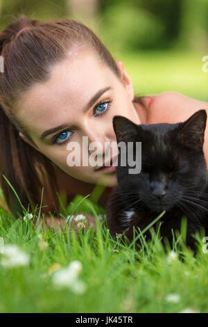 Beautiful female teenager girl young woman with blue eyes, laying down outside on grass with a black cat - Stock Photo