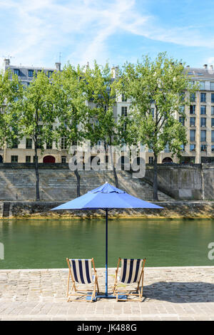 Two blue and white striped deck chairs under a blue parasol on the bank of the river Seine with poplar trees and - Stock Photo