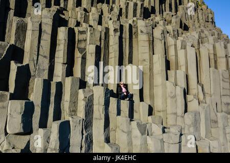 Girl sitting in middle of basalt stone columns on Reynisfjara black beach near  Vik town, Iceland on sunny summer - Stock Photo