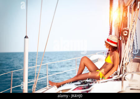 Woman relaxing on sailboat, slim model tanning on the deck of the yacht in bright sunny day, enjoying sailing adventures, - Stock Photo