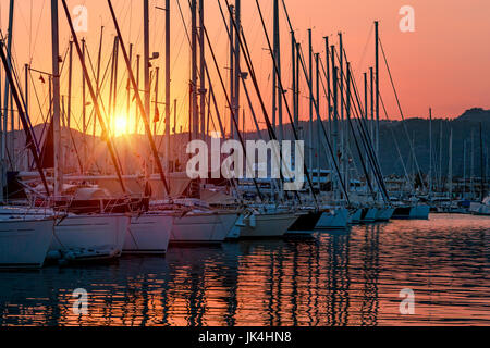Sailboats in the harbor in mild sunset light, beautiful view on the luxury water transport in the dock, summer vacation - Stock Photo