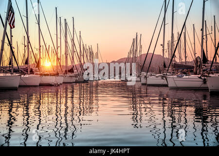 Beautiful sailboats moored in the dock, amazing view of gorgeous white sail boats over mountains background in mild - Stock Photo