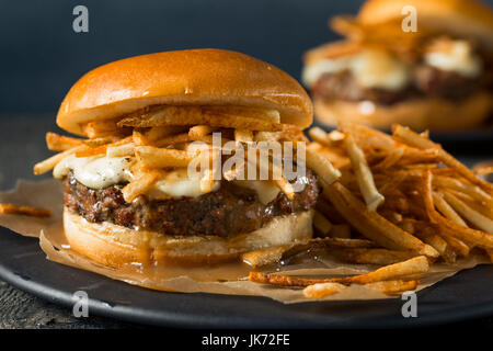 Homemade Poutine Hamburger with Fries Gravy and Cheese Curds - Stock Photo