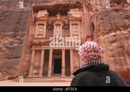 Jordan, Petra-Wadi Musa, Ancient Nabatean City of Petra, The Treasury, Al-Khazneh and man in keffiyeh headscarf, - Stock Photo