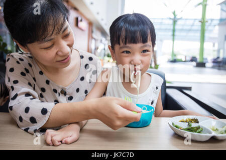 Asian Chinese mother and daughter eating beef noodles in outdoor cafe - Stock Photo