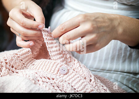 Close-up Young brunette woman with a pigtail with a deep cut on the sweater sews a button with a needle on a pink - Stock Photo