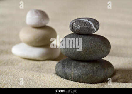 Dark and white piles of balanced stones on a sand - Stock Photo