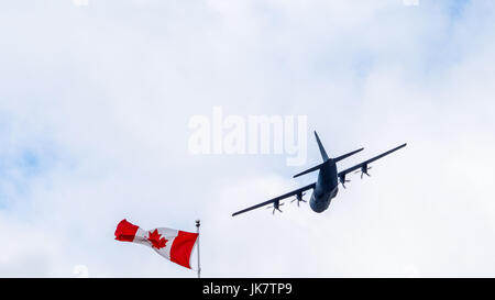 CC-130, four-engine turboprop military transport aircraft of Royal Canadian Air Force flypast the Canada Flag in - Stock Photo