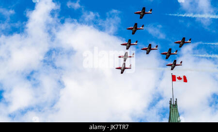 The CF Snowbirds flypast over the Canadian flag on the Peace Tower on Canada Day, Ottawa, Capital of Canada - Stock Photo