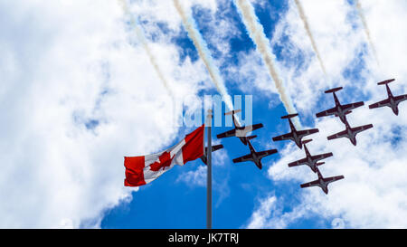 The CF Snowbirds flypast over the flag of Canada on the Canada Day in Ottawa - Stock Photo