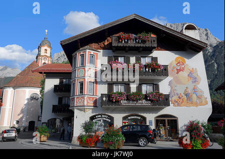 Shop with paintings and parish church St. Peter and Paul, Mittenwald, Werdenfelser Land, Bavaria, Germany - Stock Photo