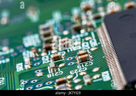 Surface mount technology (SMT) components on a green printed circuitboard. Wiring inside computer. - Stock Photo