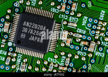 Surface mount technology (SMT) components on a green printed circuit board. Wiring inside computer. - Stock Photo