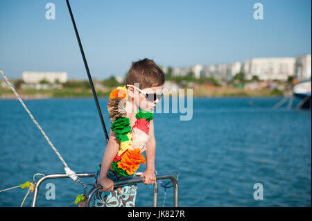 cute little boy wearing sunglasses and Hawaiian decoration on the neck aboard recreational boat - Stock Photo