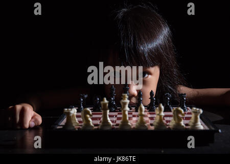 Asian Little Chinese girl playing chess in isolated black background - Stock Photo