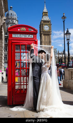 A Chinese couple pose for photographs by an Iconic red telephone box with Big Ben in the background as they celebrate - Stock Photo