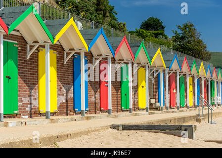 Row of colourful beach huts on a sunny day - Stock Photo