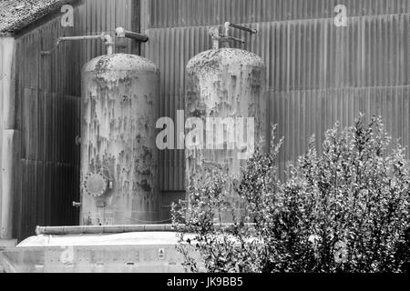Black and white image of two external high pressure cylinders involved in a manufacturing process. - Stock Photo