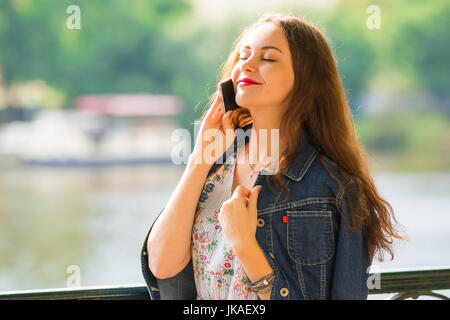 Portrait of the beautiful fashionable girl with smart phone in summer day - Stock Photo