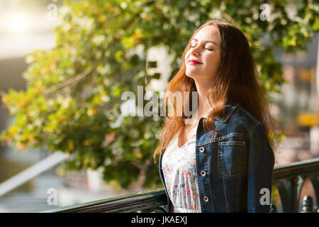 Portrait of the beautiful fashionable girl on embankment in summer day - Stock Photo