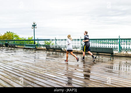 Quebec City, Canada - May 30, 2017: Two people couple, man and woman, running on wet dufferin terrace during rainy - Stock Photo